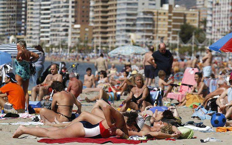 Cientos de turistas toman el sol en la playa de Levante en Benidorm. EFE/Archivo
