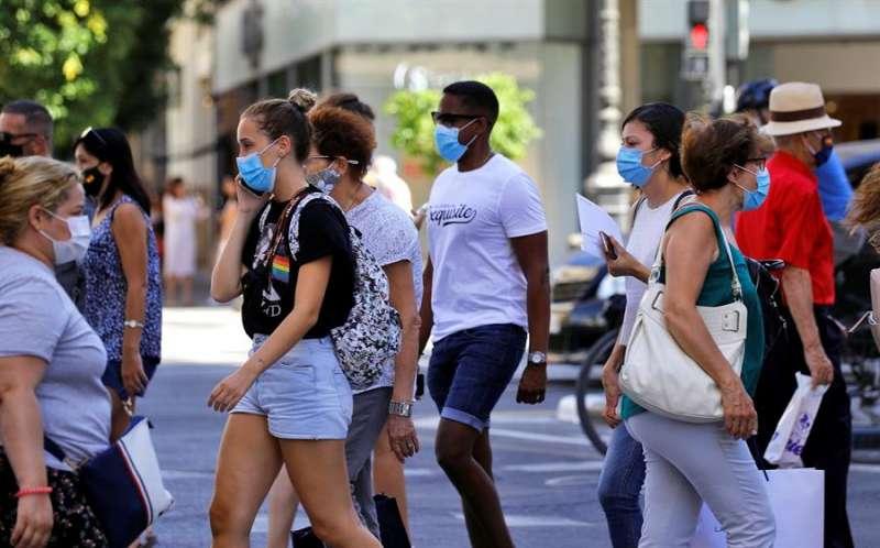 Varias personas, todas ellas con mascarilla, cruzan un paso de peatones en una calle de València. EFE
