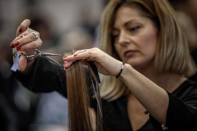 Cientos de peluqueros y peluqueras intentan batir el record Guinness de cortadores de pelo simultáneo organizado por la Asociación de Daño Cerebral Adulto y Menores (ADACAM). EFE/Biel Aliño
