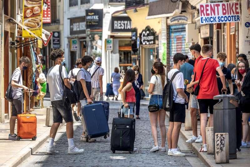 Un grupo de turistas esperan junto a sus maletas en el centro histórico de Valencia. Archivo/EFE/Biel Aliño