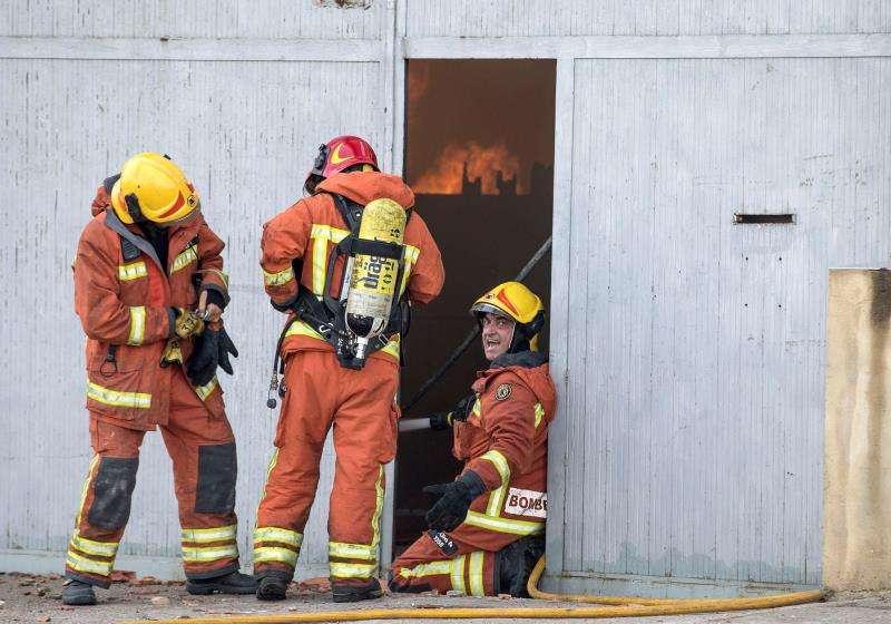 Varios bomberos trabajando en la extinción del incendio de una empresa en Valencia. EFE/Archivo