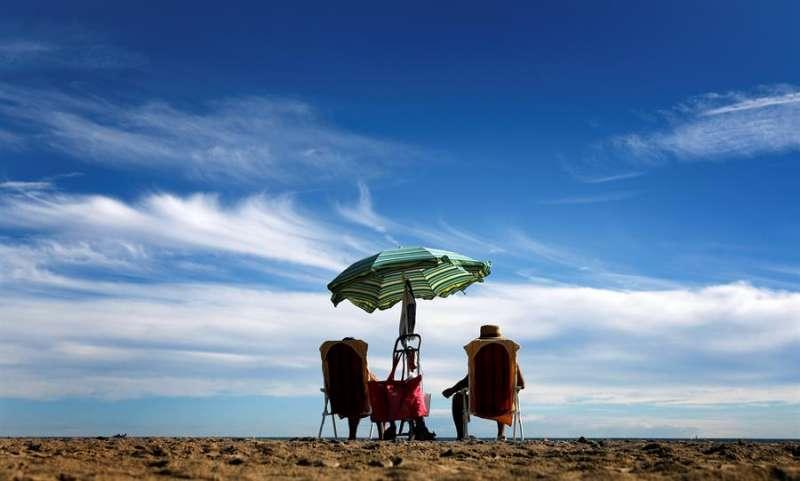 Una pareja toma el sol en la Malvarrosa EFE