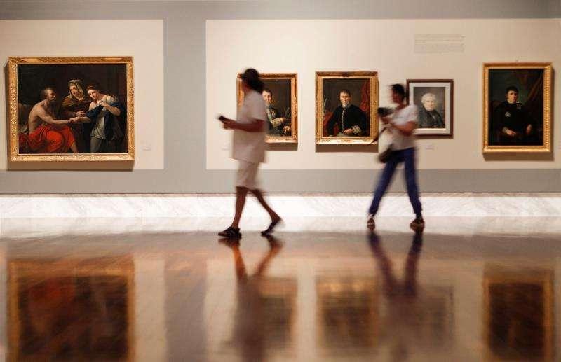 Dos personas observan varias de las obras del pintor alicantino Vicente Rodes Aries. EFE