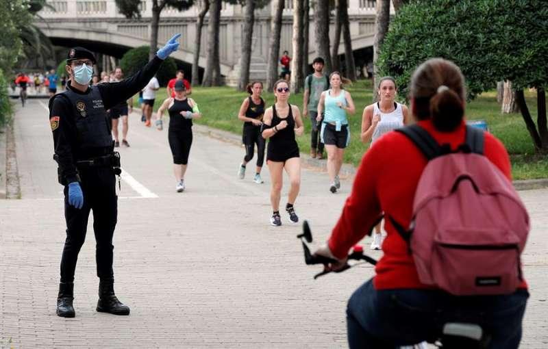 Un agente de la Policía Local ordena el sentido de circulación de los deportistas en el antiguo cauce del Turia. EFE