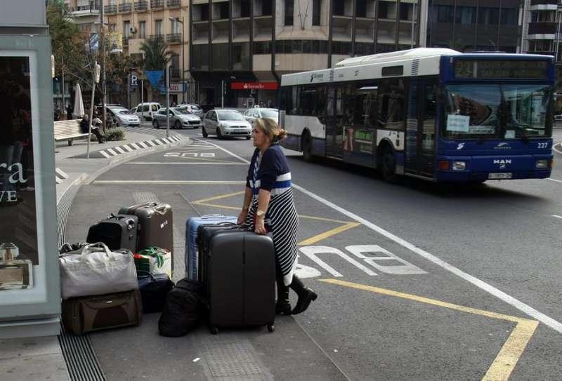 Una mujer espera en la parada del autobús de la plaza Luceros la llegada de su línea. EFE