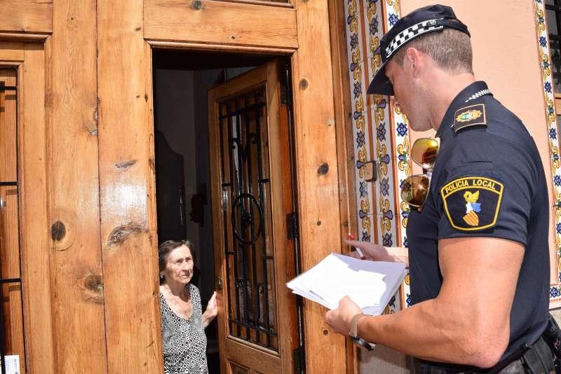 Un policia informa a una veïa.