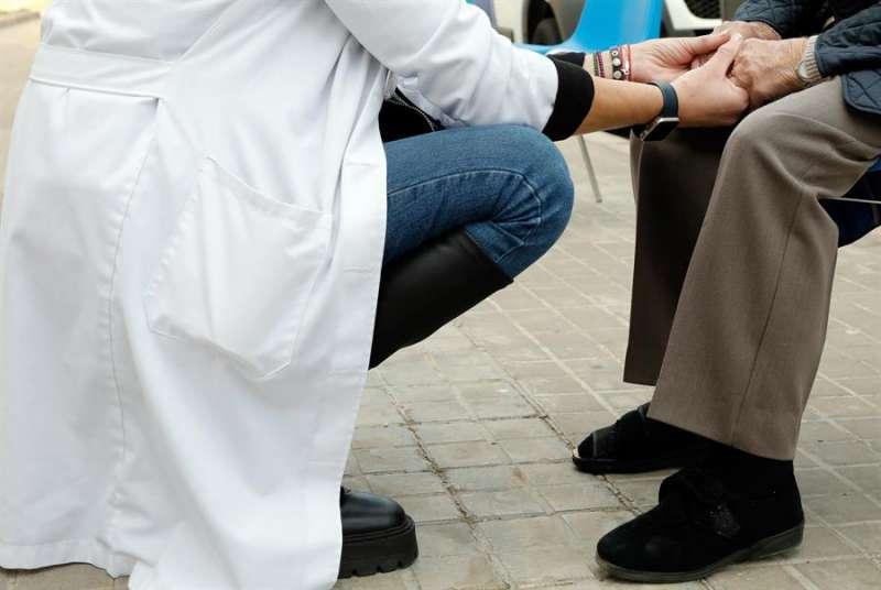 Una sanitaria conversa con una usuaria de una residencia de València momentos antes de inyectarle la vacuna. EFE/Juan Carlos Cárdenas/Archivo