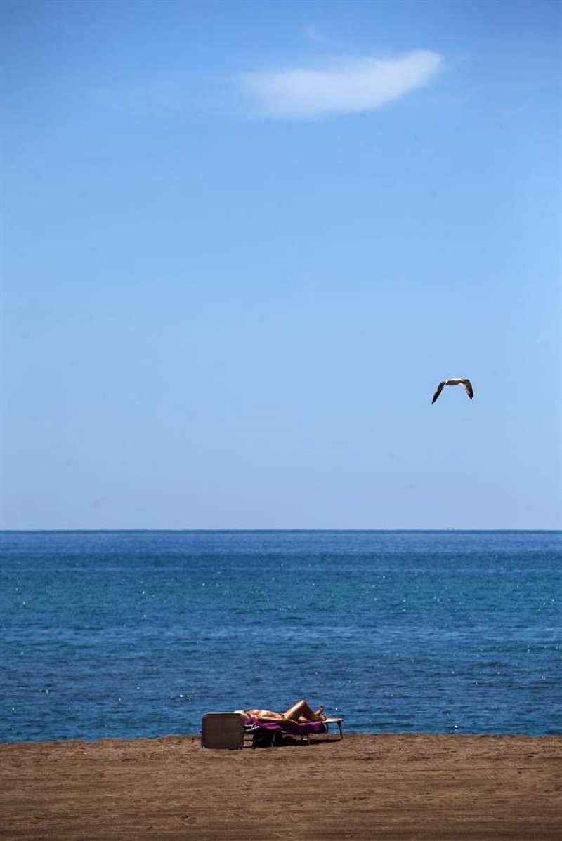 Una persona toma el sol en la playa. EFE