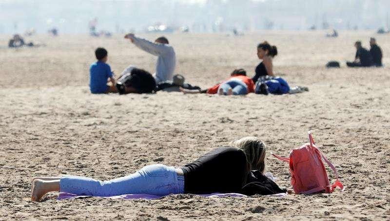 Varias personas disfrutan de la playa. EFE