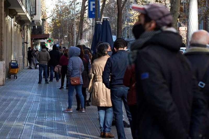 Multitud de personas hacen cola para realizarse un test PCR en un laboratorio de Barcelona este lunes9. EFE/Alejandro García.