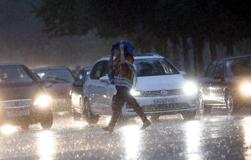 Una mujer se protege con una bolsa de las fuertes lluvias. EFE/Archivo Kai Försterling