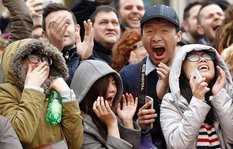 Unos turistas asiáticos reaccionan ante el estruendo del disparo de la última mascletà de las Fallas. EFE