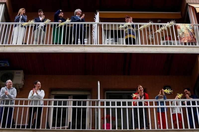 Vecinos de Elche decoran sus balcones con improvisadas palmas y salen a aplaudir en el momento en el que redoblan las campanas por el Domingo de Ramos. EFE/Manuel Lorenzo