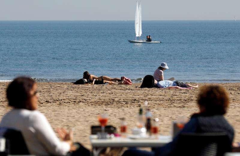 Varias personas disfrutan del buen tiempo y de las altas temperaturas en la playa de la Malvarrosa. EFE