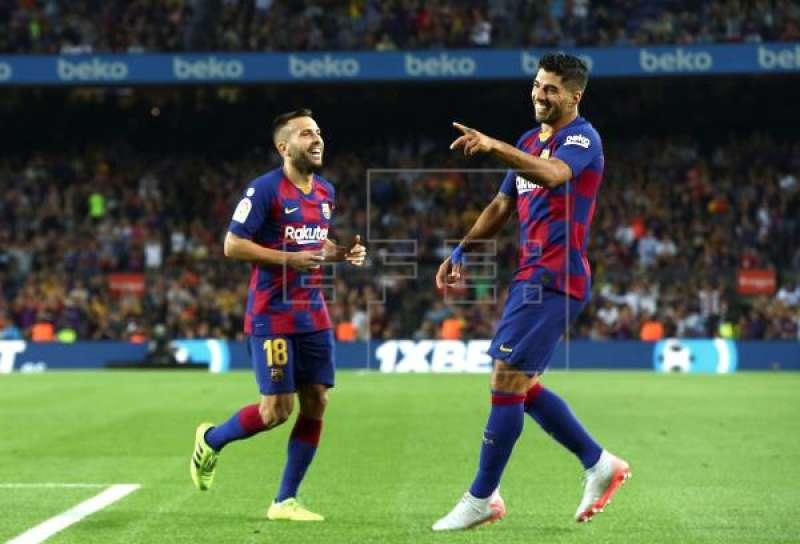 El delantero uruguayo FC Barcelona Luis Suárez celebra junto a Jordi Alba (i) tras marcar el quinto gol ante el Valencia, durante el partido de la cuarta jornada de Liga en Primera División disputado en el estadio Camp Nou, en Barcelona. EFE/Enric Fontcuberta
