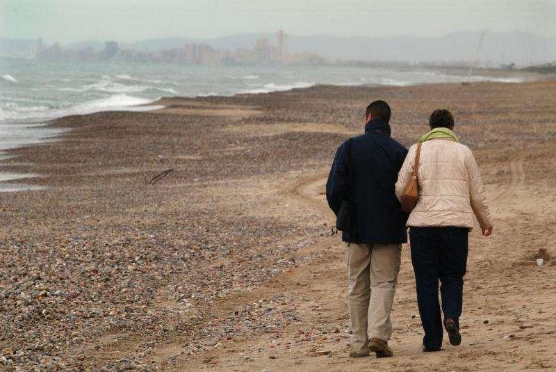 Una pareja pasea por la playa prácticamente desierta de