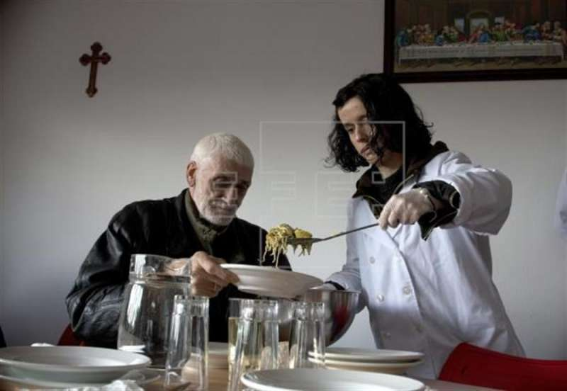 Una voluntaria sirve comida a una persona sin recursos en un comedor social. EFE/Archivo