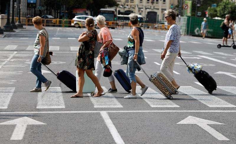 En la imagen, varias turistas arrastran sus maletas tras abandonar el hotel, en València. EFE