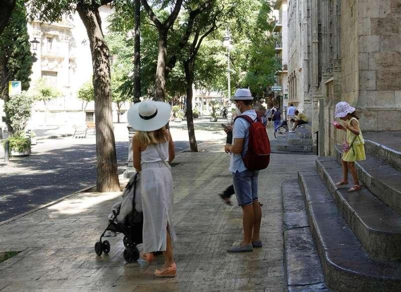 Una familia de turistas pasea junto al edificio de La Lonja, Patrimonio de la Humanidad, en el centro histórico de Valéncia. EFE/Manuel Bruque