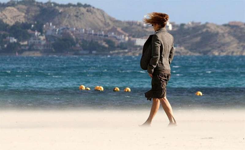 Una mujer joven pasea por la Playa del Postiguet de Alicante en una jornada de fuerte viento