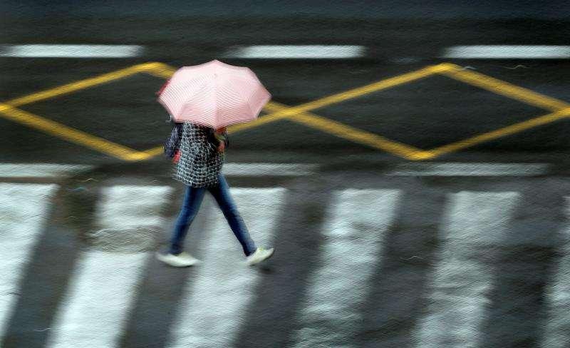 En la imagen, una persona se protege de la lluvia en la ciudad de València, hoy a primera hora del día. EFE