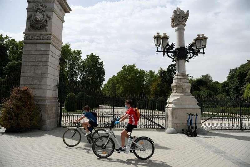 Dos jóvenes montan en bici en el exterior del parque del Retiro en Madrid. EFE/ Víctor Lerena/Archivo