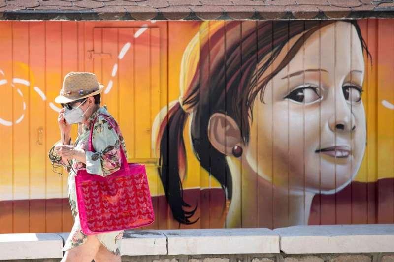 Una persona con mascarilla camina delante de un mural. EFE/Archivo