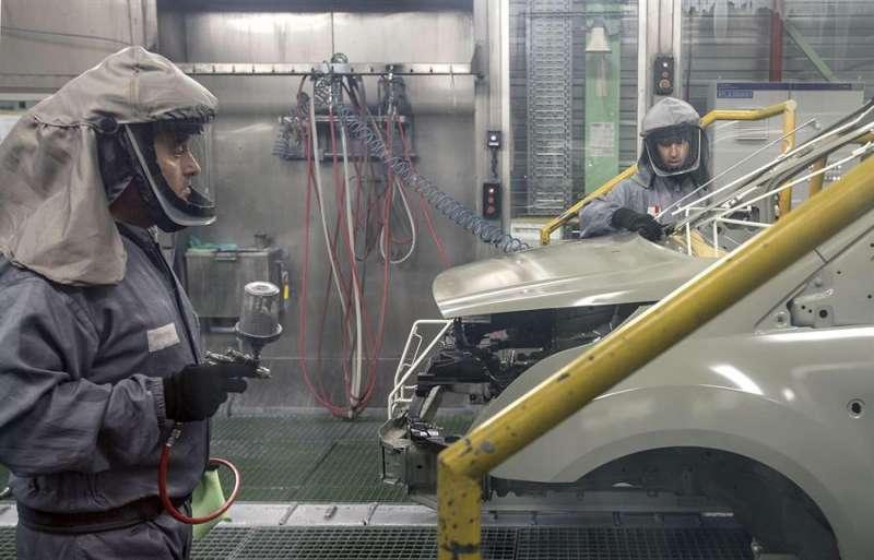 Dos trabajadores de la planta de pintura de Ford en Almussafes (Valencia) revisan una carrocería. EFE