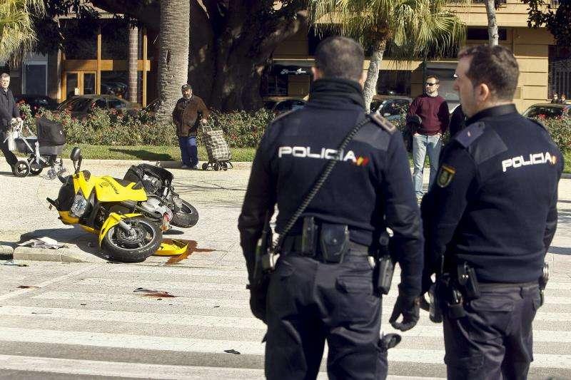 Dos policías nacionales observan el lugar de una colisión de un turismo y una motocicleta, con el resultado de cinco personas heridas de diversa consideración. EFE/Archivo