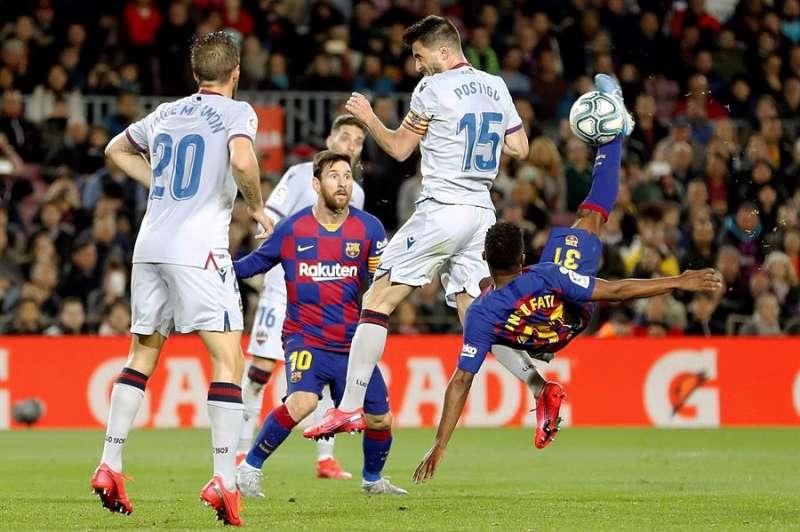 El delantero del FC Barcelona Ansu Fati (d) remata ante Sergio Postigo (2-d), del Levante. EFE/Alberto Estévez