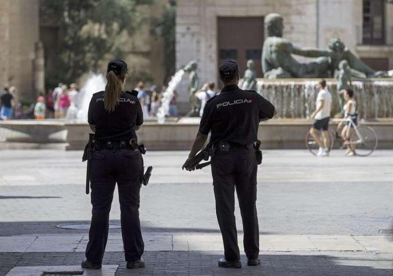 Dos agentes de la Policía Nacional patrullan por la Plaza de la Virgen de València en una imagen de archivo. EFE/Manuel Bruque/Archivo