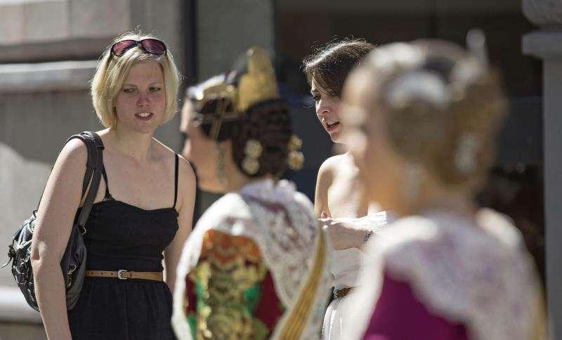 Dos jóvenes turistas observan a las falleras de una comisión en un pasacalle por el centro de Valencia. EFE/Archivo