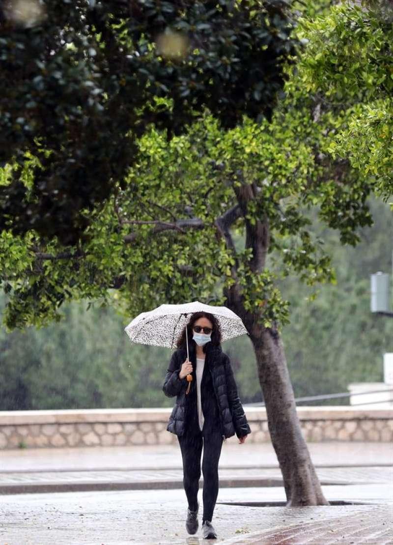 Una persona pasea con mascarilla y paraguas bajo la lluvia, estos días. EFE/Ana Escobar