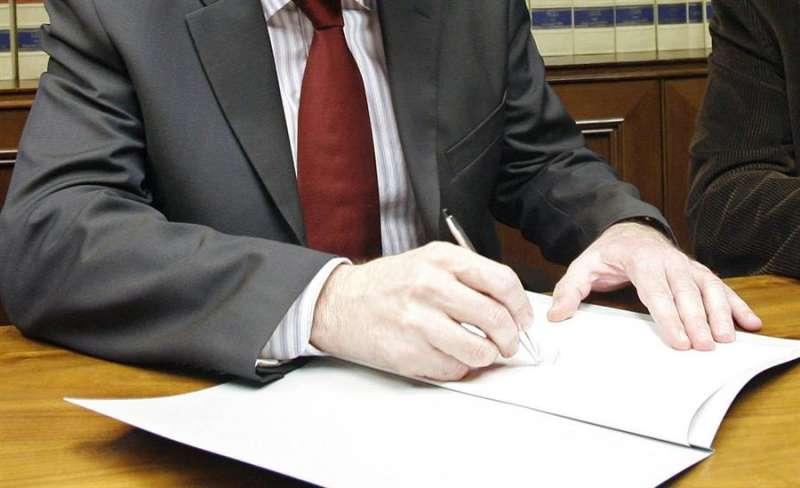 Una persona firma documentos en una notaría. EFE/Archivo