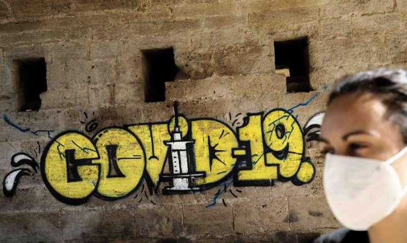 Una persona con mascarilla pasa ante un grafiti este miércoles en Valencia EFE