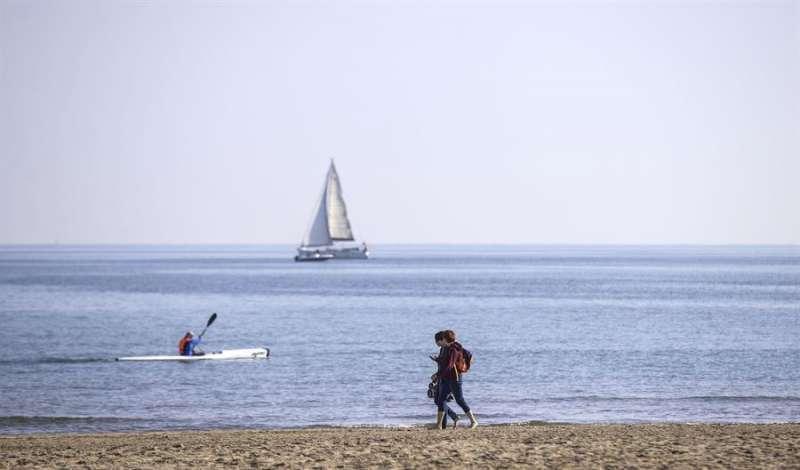 Un hombre navega en su kayak cerca de la orilla de la playa de La Malvarrosa de València, mientras una pareja pasea disfrutando de temperaturas suaves. EFE/Manuel Bruque/Archivo