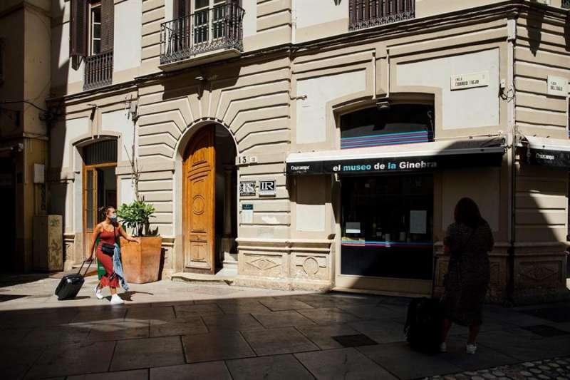 Varios turistas con maletas caminan por el centro de Málaga, ayer lunes en el primer día laborable de la