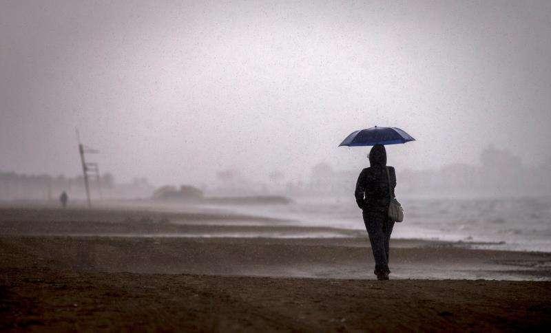Una persona pasea por la playa de la Malva-rosa de València bajo la lluvia. EFE/Archivo