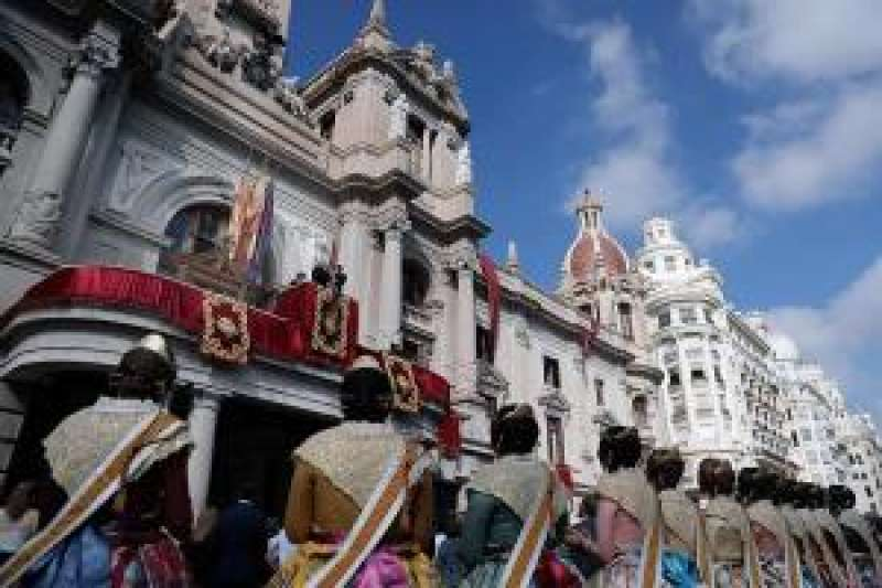 Decenas de falleras observan la bajada de la Real Senyera del balcón del Ayuntamiento de València , desde donde se inicia la procesión cívica del 9 d