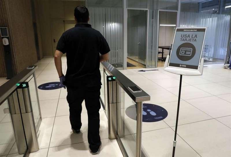 Un trabajador ficha al entrar a su oficina. EFE