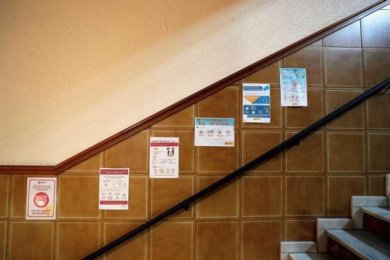Numerosos carteles en una escalera del colegio de Valencia con información de medidas sanitarias. EFE/Manuel Bruque