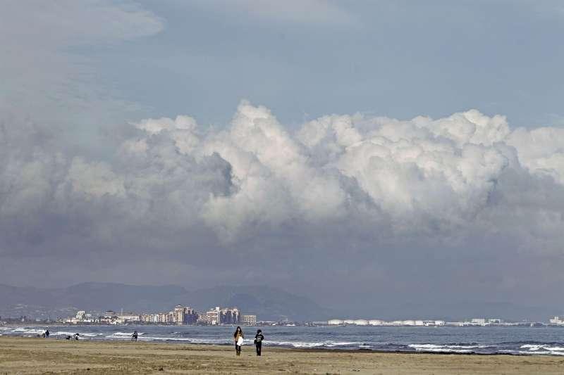Una pareja pasea por la orilla de la playa de Las Arenas de Valencia.