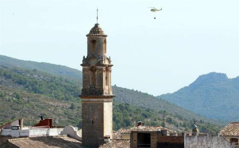 Un helicóptero se dirige a cargar agua en el incendio que comenzó ayer en Villalonga (Valencia) y pasó a la provincia de Alicante por la Vall de la Gallinera. EFE/ Natxo Francés