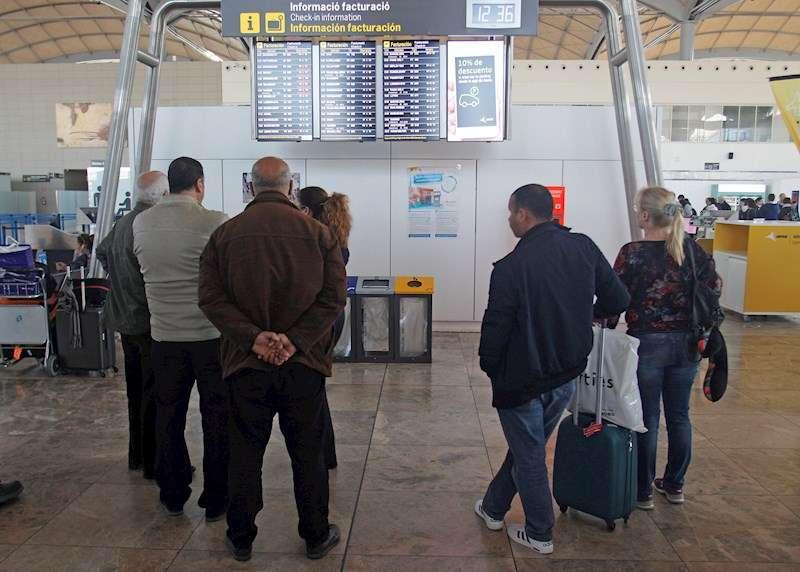 Pasajeros del aeropuerto de Alicante-Elche se informan en los paneles para poder embarcar. EFE