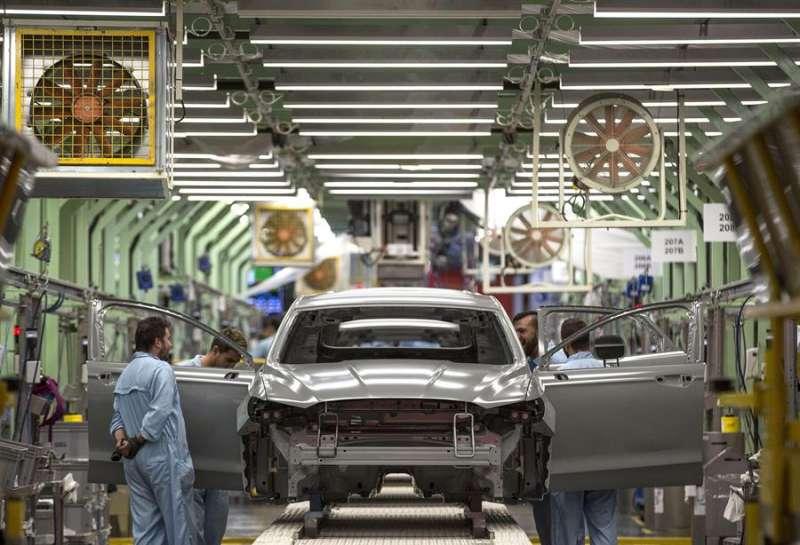 Varios trabajadores de la planta de pintura de Ford en Almussafes (Valencia), revisan una carrocería tras su paso por la zona de pintura.