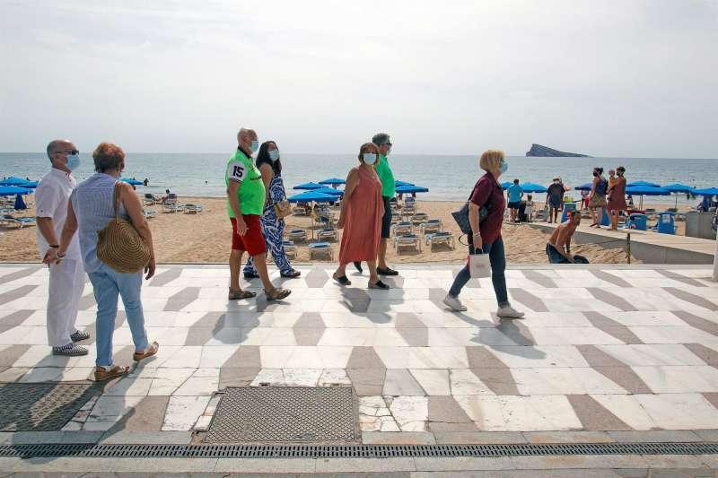 Un grupo de turistas pasea por la playa de Levante de Benidorm