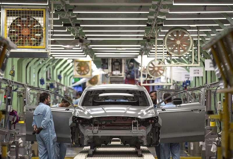 Varios trabajadores de la planta de pintura de Ford en Almussafes, revisan una carrocería tras su paso por la zona de pintura. EFE