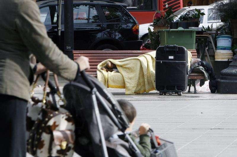 Un sintecho duerme en un banco en un parque de València. EFE/Archivo