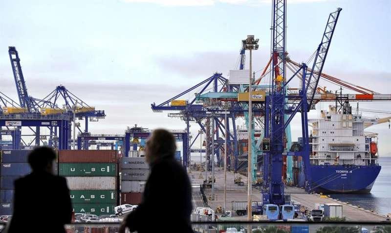 Dos personas observan los trabajos de estiba en varios barcos en el puerto de València. EFE/Archivo/Manuel Bruque