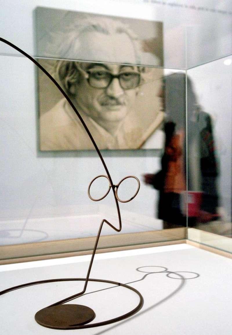 Una joven pasa entre un retrato del ensayista valenciano Joan Fuster y una escultura que muestra su perfil. EFE/Archivo